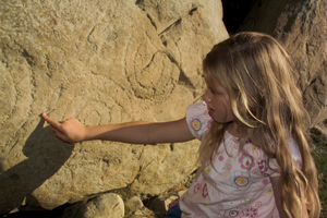 Girl tracing Spirals at New grange Kerbstone, County Meath, Ireland