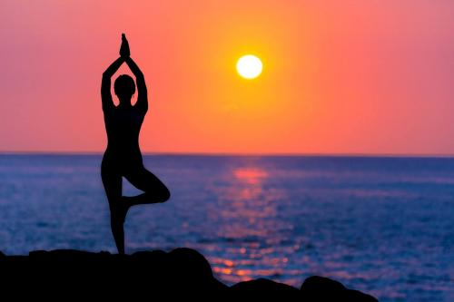 person holding a yoga pose on a beach while the sun is setting