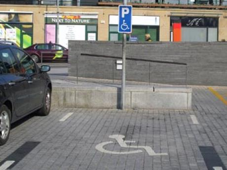 accessible parking bay showing markings and blue sign with accessible logo
